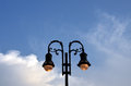Street lamp ornate lit against blue sky Royalty Free Stock Photos