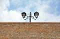 Street lamp over brick wall on the top of a shaped on the sky Stock Images