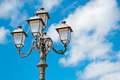 Street lamp under a blue cloudy sky Stock Images