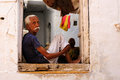 Street life of india jaisamler march indian sitting in the window his house by the town s main jaisamler in march Stock Photography