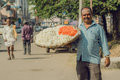 Street life and man with huge tray of flowers for indian puja on