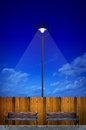 Street lighting with bench and wooden fence Stock Photography