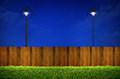 Street lighting and wooden fence with shrub Royalty Free Stock Photo