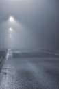 Street lights foggy misty night lamp post lanterns deserted road in mist fog wet asphalt tarmac car headlights approaching blue Stock Photo