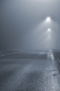 Street lights, foggy misty night, lamp post lanterns, deserted road in mist fog, wet asphalt tarmac, car headlights approaching Royalty Free Stock Photo