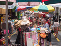 Street market in busan south korea stand with beach umbrella selling hats the foreground sale persons and customers passing by Stock Images