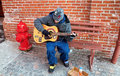 Street musician lancaster pa usa january playing his guitar for a pittance in sub freezing temperatures near the entrance to Stock Photography