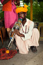 Street performer plays on traditional indian musical instrument in haridwar india Stock Photo