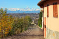 Street runs through small italian town narrow typical of santa vittoria d alba as snowy mountain peaks on background in piedmont Royalty Free Stock Photos