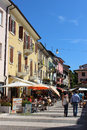 Street scene with cafes etc lazise by lake garda view along a in on a hot sunny summer day tourists and holidaymakers enjoying the Stock Images