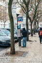 Street scene with male paying for the parking at the meter in a residential area Royalty Free Stock Photo