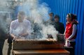 Street side food vendor grills meat skewers shanghai china february a tends to his grilling on a line of buyers wait and watch as Stock Photography