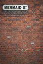 Street sign background mermaid st rye uk old fashioned for in east sussex mounted high on brick wall Royalty Free Stock Image
