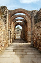 Street with stone arches vertical to the bottom are some palm trees remnants of the ancient roman civilization was in spain in Stock Photo