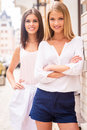 Street style beauties two beautiful young well dressed women smiling at camera while standing close to each other outdoors Stock Images