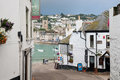Street to harbor edge past cafe shops and apartments leading down st ives Stock Photo
