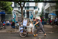 Street vendor pushing a cart vietnamese pushes full of plastic stools and buckets on the streets of ho chi minh city she is Royalty Free Stock Images