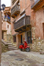 Street view of albarracin spain with red houses and scooter in Royalty Free Stock Images