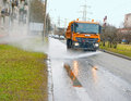 Street watering and cleaning the roadway using machine Royalty Free Stock Photo