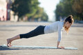 Street yoga plank pose in the city beautiful young sporty woman wearing sportswear working out on the on summer day doing posture Royalty Free Stock Images