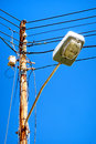 Streetlamp and electric cables in front of blue sky Stock Images