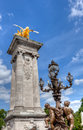 Streetlamps and column with golden winged horse in Paris Royalty Free Stock Photo