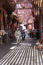 The streets of marrakech a narrow alley a man cycling among shops city Stock Photo