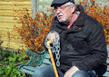 Stress of old age an man sitting looking miserable and chained to his walking stick because his and infirmity Royalty Free Stock Images