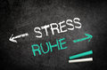 Stress and ruhe concept written on a blackboard conceptual silence message black chalkboard with chalk sticks in the lower right Stock Photography