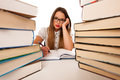 Stressed asian caucasian woman student learning in tons of books Royalty Free Stock Photo