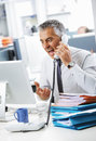 Stressed business man shouting at phone in office Stock Photography