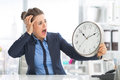Stressed business woman looking on clock in office Royalty Free Stock Photos