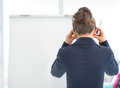 Stressed business woman near flipchart rear view in office Stock Image