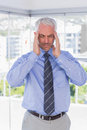 Stressed businessman rubbing his temples with eyes closed standing in office Royalty Free Stock Photo