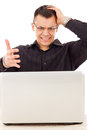 Stressed casual man with glasses looking at laptop in black shirt Royalty Free Stock Photo