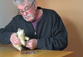 Stressed elderly man emptying piggy bank a pensioner money from his he is counting the money to see if he has enough to pay his Stock Photo