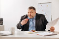 Stressed employee stuffing himself with baked sweets Royalty Free Stock Photo