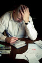 Stressed man with checkbook struggling while working on household finances Royalty Free Stock Photography