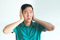 Stressed man covering his ears and do not want to hear, noise too loud.