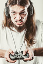 Stressed man playing on pad addiction depressed young gaming angry guy with controller play console face expression Royalty Free Stock Images