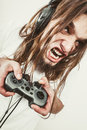 Stressed man playing on pad addiction depressed young gaming angry guy with controller play console face expression Stock Photography
