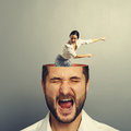 Stressed man with screaming woman men open head young women standing into the head looking at the men and showing the direction Royalty Free Stock Photo