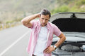 Stressed man waiting assistance after a car breakdown at the side of the road Royalty Free Stock Photos