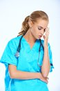 Stressed nurse or doctor with a headache Royalty Free Stock Photo