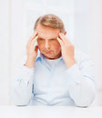 Stressed old man holding head at home oldness business and people concept Stock Photos