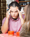 Stressed out man holding head men rubbing his at table with friend Stock Image
