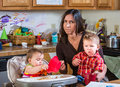 Stressed out mother in kitchen with her babies Stock Photography