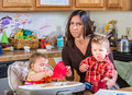 Stressed out mother in kitchen with her babies Stock Photo