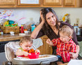 Stressed out mother in kitchen with her babies Stock Images