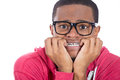 A stressed out nervous black nerd closeup portrait of young nerdy unhappy guy with glasses biting his nails and looking to camera Royalty Free Stock Images